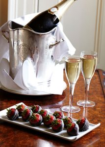 chillled wine bucket with two glasses of white wine beside it and a plate of chocolate covered strawberries