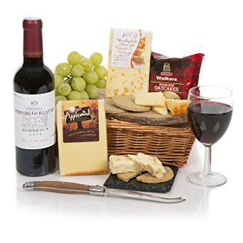 An assortment of cheeses, cured meats, fruit and crackers in a basket