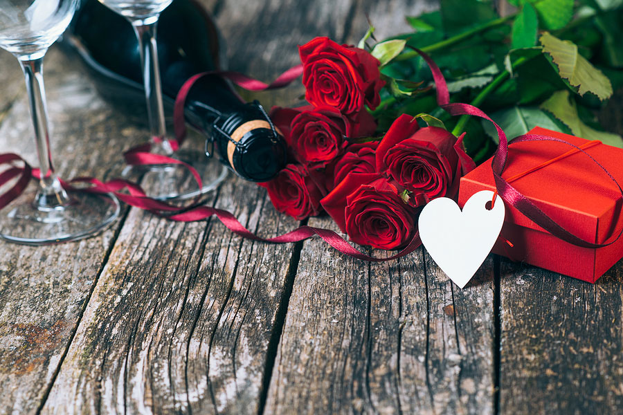 Beautiful red roses, Valentines gift with flowers, Champagne glasses and romantic roses on wooden boards