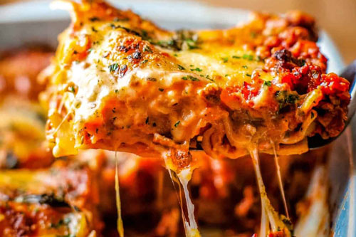 fresh lasagna being served from a dish